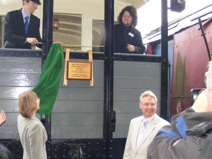 The plaque on IVAN being unveiled, 30th July 2008. In the van are James and Ben, who both worked on the project. Tugging at the flag/curtain is Catherine Mason. Mark Cosgrove, deputy Mayor of Carrickfergus, applauds the unveiling while Sandy Smith of the International Fund for Ireland looks on in approval.