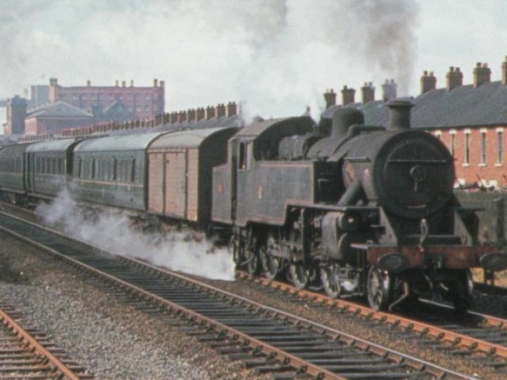 A classic NCC scene! No.4 and train, with brown van in front, accelerates away from Belfast York Road on 2nd July 1966 with a Sunday School special for Portrush. (D.Young)