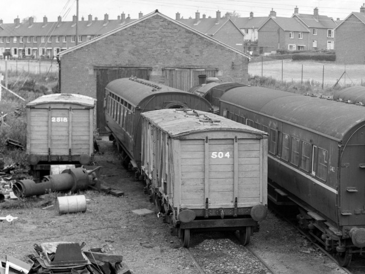 July 1977: Guinness Vans 2518 (derailed and acting as a wood store) and 504 in front of the shed at Whitehead. (C.P. Friel)