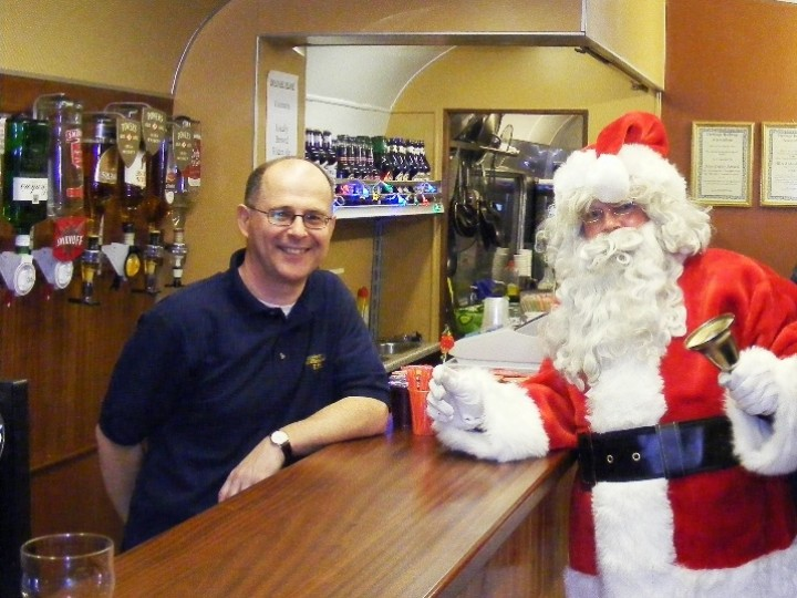 5/12/2009: Finally, the bar in action. Santa gets a warm welcome from Paul the barman on a 'Santa Special' train. (C.P.Friel)