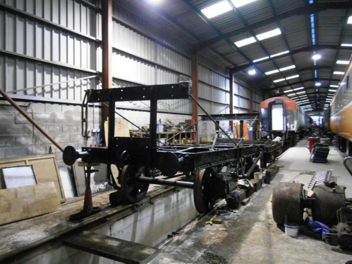 On 8th November 2016 the frames have been shunted over the pit in Carriage Shed A-Road and cleaning and painting is virtually finished. The wooden cradle has been removed and pieces can be seen beside the frames. Some can be re-used, most were too far gone and will be re-made by HEI. The corners at the Belfast end are being alternately jacked up to permit bearing insertion; this has raised the height of the frames nearest the camera by around 4 inches back to where they should be and the slope to Larne can clearly be seen, the wagon's buffers at that end being only level with the spare Mk2 Bogie behind them. (M.Walsh)