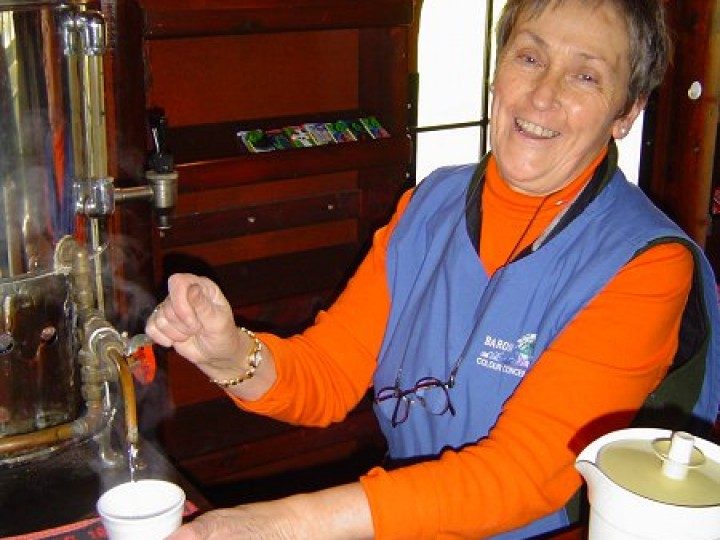 In the tea bar on 87's last trip on the main line, Rita Henderson prepares another cup of coffee. While in the bar, another pint is pulled for a passenger. Rita and the rest of the dining car staff had to wait 4 years before we had a steel bodied dining car ready (547) to take 87's place on our steam trains.