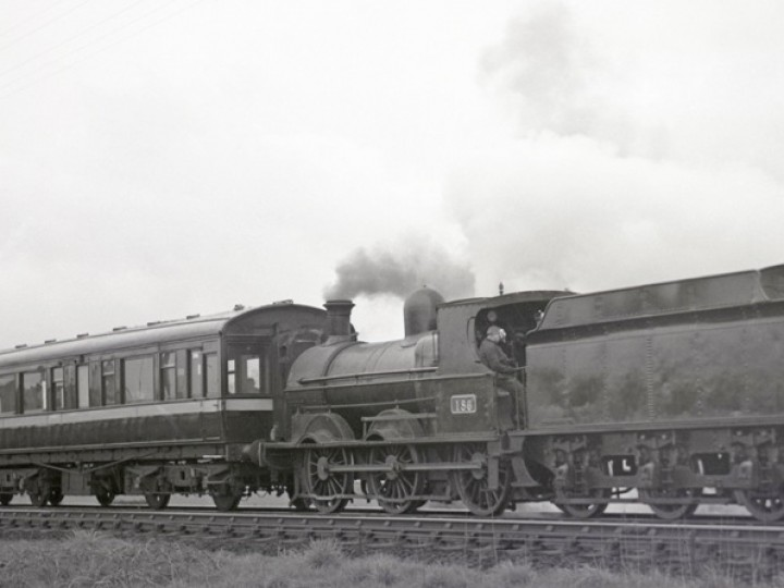 Driver Mosey Simpson mops his brow on the footplate of No.186 while waiting for the road at Knockmore Junction on Sunday 5/5/1968. Carriages 150 and 198 make up the train. (C.P.Friel)